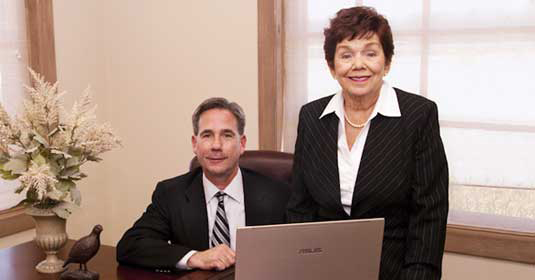 Jim Stanton and Carmen Stanton smiling at a desk in Career Employment Service, Inc.